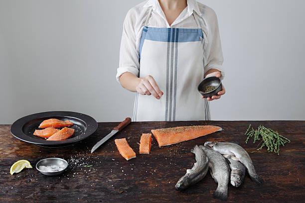 Chef cuisinier qui prépare une recette à base de saumon